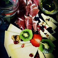 Excellent Aperol Spritz and combination of prosciutto, cheese, strawberries, kiwi and nuts that