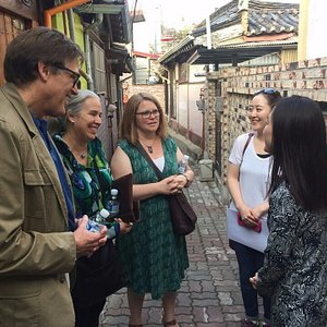 American business travelers walk to Seochon village with a local host