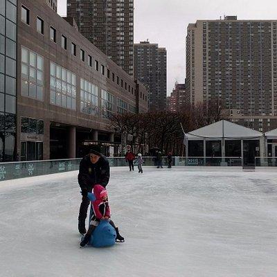 Mi hijo con la hija de nuestros amigos en la pista de patinaje sobre el hielo