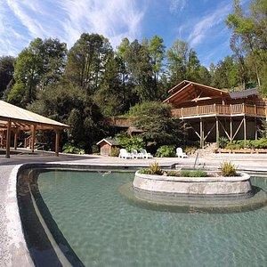 piscinas aire libre en primer plano. Arriba restaurant y al costado izquierdo piscina sólo techo