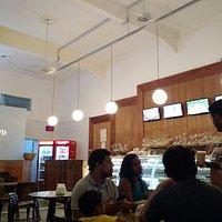 Parte interna da padaria, com mesas para uso dos clientes