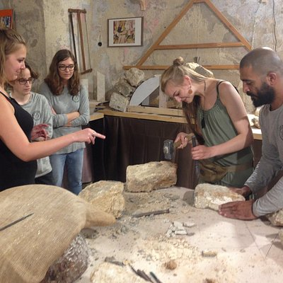tourist enjoys the touch of the traditional stone carving tools