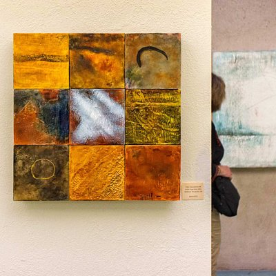 Visitor views diverse works of encaustic art at the museum.