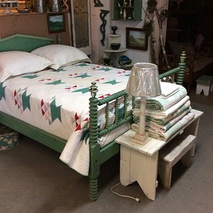 Beautiful old quilt on this fun antique bed.