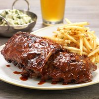 MESQUITE-GRILLED BABY BACK RIBS  Wood-Fired, Salt Creek Grille BBQ, Kale Slaw, Asiago Garlic Fri
