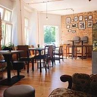 Café mit gemütlichen Sitzplätzen, Couch und Mooswand