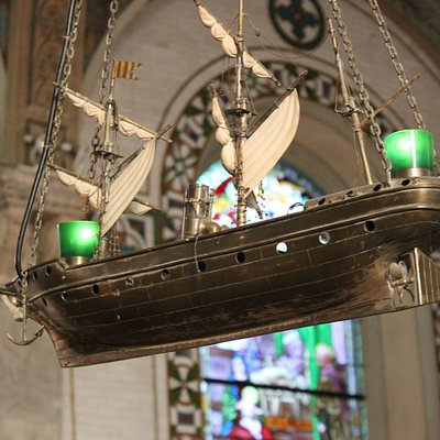 Stained-glass window and miniature boat hanging from the vault.