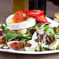 Ensalada de queso de cabra con fruta de temporada y mermelada de tomate.