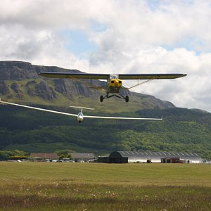 Tugg plane pulling a glider with Binevinagh mountain in the background