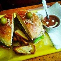 Hamburguesa presentada con pan tostado y salsa
