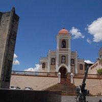 Há dois monumentos bem em frente a igreja, que fica recuada em relação rua