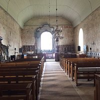 Inside the Isokyrö church shows the wall paintings and wooden statues in the front.