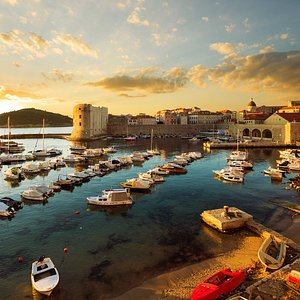 Dubrovnik's harbour and walls glow at sunset. Let our guides find you the best views!