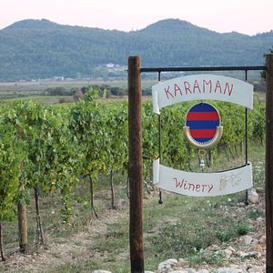 The sign of Malvasija Karaman Winery in their beautiful wineyard surrounded by heavenly scenery