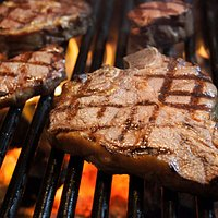 Porterhouse and other USDA Prime cuts on our Kiawe wood broiler.