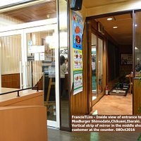 Inside view of entrance to MosBurger Shimodate,Chikusei. Mirror shows customer at counter.