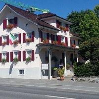 Ein Restaurant / Hotel mit einer Gartenwirtschaft in der alte Kastanienbäume Schatten spenden