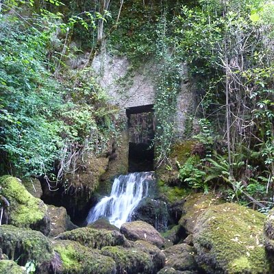Por la puerta del antiguo molino en ruinas sale una de las cascadas