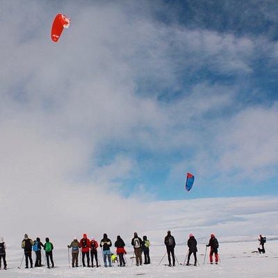 En grupp turskidåkare i möte med ett Snowkitegäng en härlig dag i april