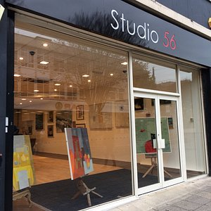 Contemporary paintings behind bland shop front.