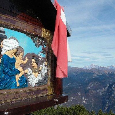 Particolare del dipinto della croce con sullo sfondo le Dolomiti