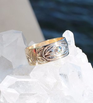 Mowisaht Designs Jewelry on-site. 14k gold ring set with a diamond and engraved with Thunderbird