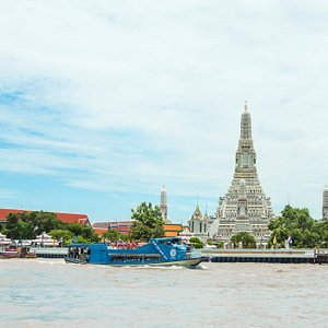 Chao Phraya Tourist Boat's double-decker boat passing the Temple of Dawn (Wat Arun)