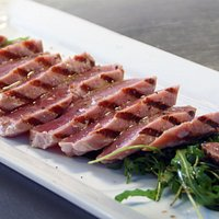 Tagliatta de atún con jugo de limón, aceite de olivo y pimienta, servida sobre una cama de arúgu