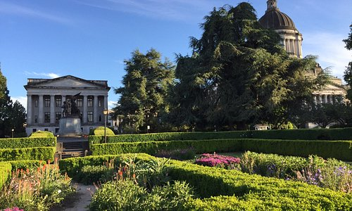 Gardens on the grounds with war monument, capital building and justice hall in background- beaut