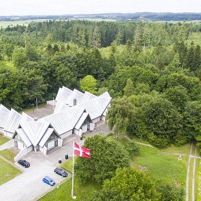 Luftfoto af Dronninglund Kunstcenter i grønne omgivelser.
