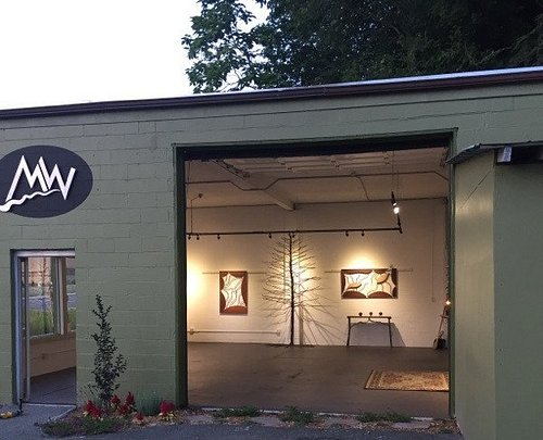 View into MW Studios gallery, featuring large metal tree sculpture, wall hangings, etc.