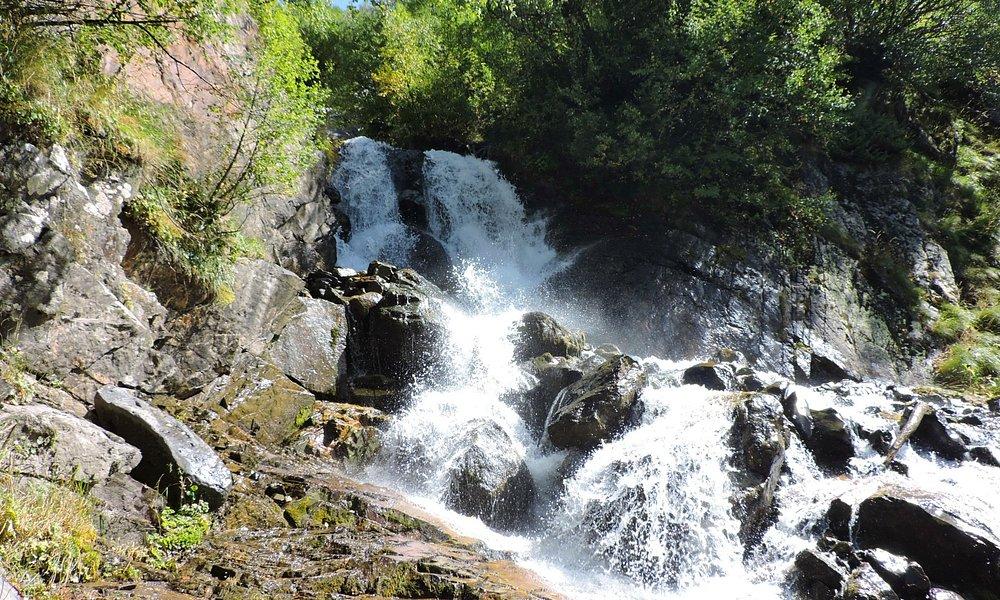 Водопад расположен не на открытых скалах, а среди деревьев