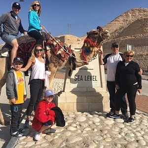 Family with a camel at sea level