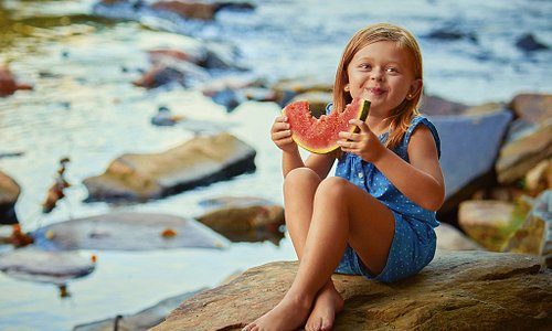 Young girl taking a bite out of summer on the Toccoa River.