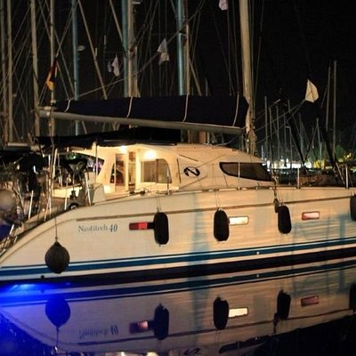 RED FOX Catamaran by night with under-water light