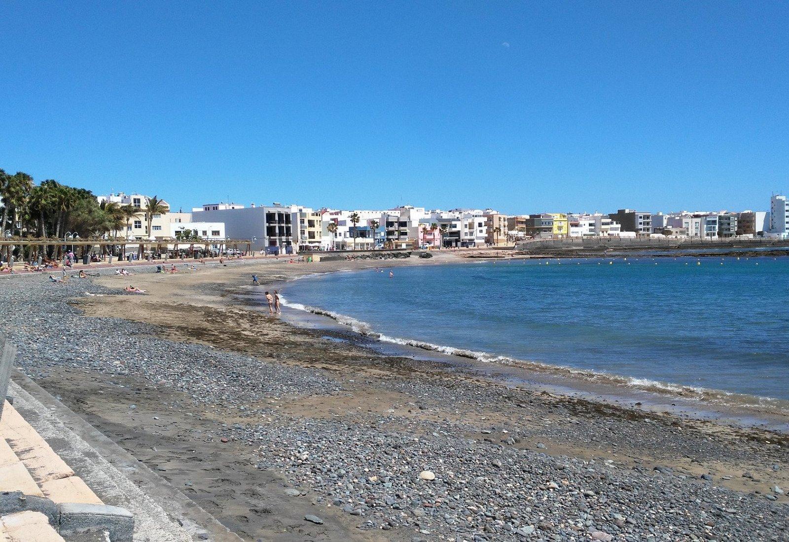 Playa de Arinaga. De piedra negra y rocas. Grande. Buenos servicios