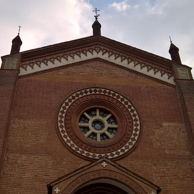 La facciata a capanna con rosone e torrette con banderuole segnavento e croce della Chiesa