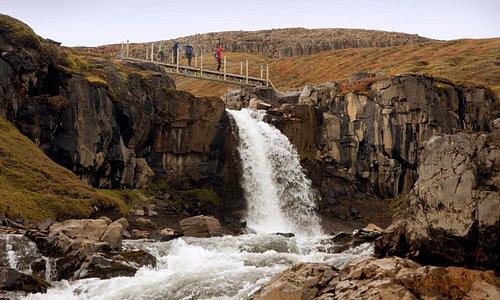 Hiking bridge over small waterfall
