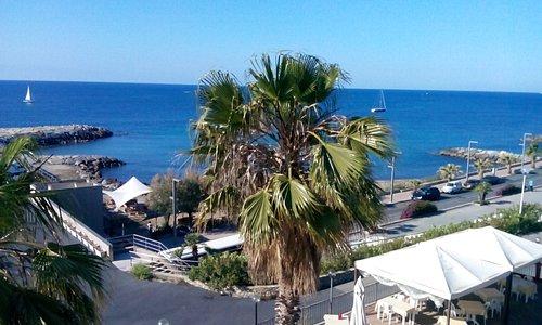 Camera tra la spiaggia, il mare, il porto di Marina degli Aregai e la pista ciclabile.