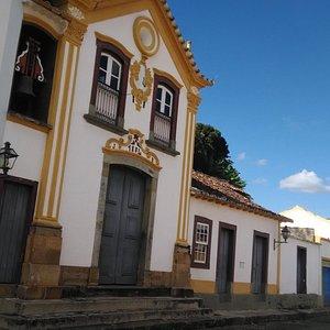 A capela e seu sino entre o casario colonial.
