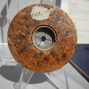 A compass circa 1836 - 1854 that is made of laquer, wood, glass, metal and ink.