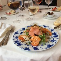 A duo of cooked and smoked salmon served on a fresh salad, dressed with capers and home made dre