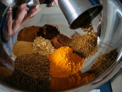 Freshly grinding whole spices to handcraft the Sweet Curry Powder spice blend.