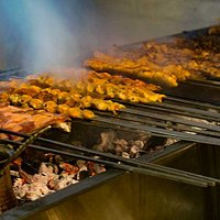 freshly prepared meat cooking over real charcoal grill.