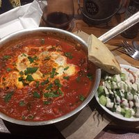 Shakshuka. Two eggs poached in the pan in homemade sauce tomatoes with pita and Israeli salad.
