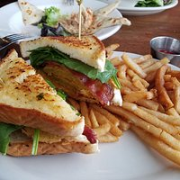 Fried green tomato club sandwich with tomato jam. In the background is the smoked tuna dip.