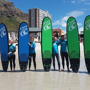 Group learn to surf lesson with the Surfshack crew at beautiful Muizenberg beach. www.surfshack.