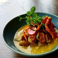 Gnocchi with Jalapeno Corn Broth garnished with pickled vegetables and crispy prosciutto