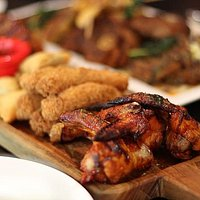 Grille mixed tapas. Roasted chicken wings, fried fish fingers, samosa  and tangy sauce to dip.