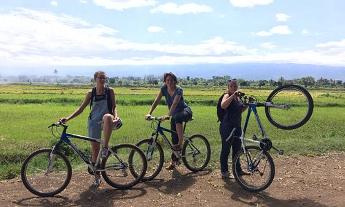 One Trip One Tree cycling, happy clientts during Rau forest and rice paddies in Moshi